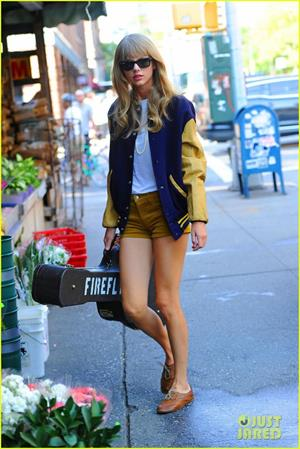 Taylor Swift carrying her guitar and showing off her legs in NYC, August 31st, 2012.  She is wearing a purple and gold jacket and shorts.  Her guitar case has the word  Firefly  on it
