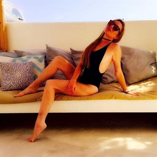 Lindsay posing on a bench filled with pillows; her classic suit adorned with a necklet.