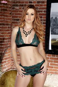 Karlie Montana in green and black lingerie in front of a brick wall