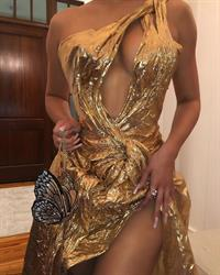 Kylie Jenner in sexy gold dress showing off her braless boobs cleavage going to Justin Bieber and Hailey Bieber's wedding.