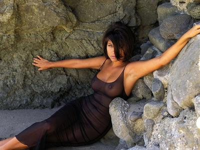tiffani thiessen posing at the beach in a see through dress.